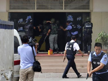 "A handout picture shows armed policemen trying to rescue hostages at a police station during a clash in Hotan, Xinjiang Uygur Autonomous Region July 18, 2011. China on Wednesday raised the death toll to 18 from the clash at the police station in the restive far western region of Xinjiang, saying that 14 ""rioters"" died along with two policemen and two hostages in the worst violence there in a year.   Xinjiang Public Security Bureau/Handout/Reuters."