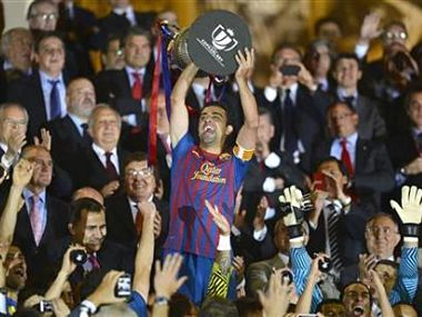Barcelona's Xavi Hernandez lifts up the Spanish King's Cup trophy after winning their final against Athletic Bilbao. Reuters