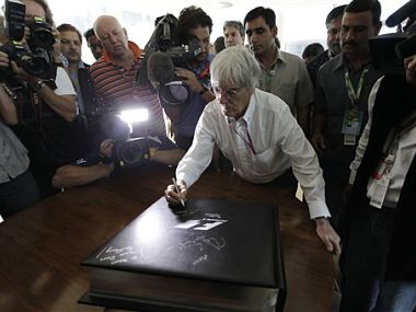 Formula One chief Bernie Ecclestone autographs a book on the history of formula one. AP