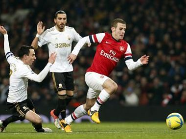 Arsenal's Jack Wilshere runs past Swansea City's Chico Flores and Leon Britton during their FA Cup third round replay soccer match at the Emirates Stadium in London