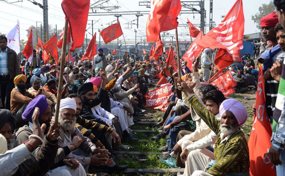 """Activists from various trade unions block the tracks during a two-day strike opposing the current UPA government's economic policies at the railway station in  Amritsar on 20 February, 2013. Millions of India's workers walked off their jobs in a two-day nationwide strike called by trade unions to protest at the """"anti-labour"""" policies of the embattled government. AFP"""