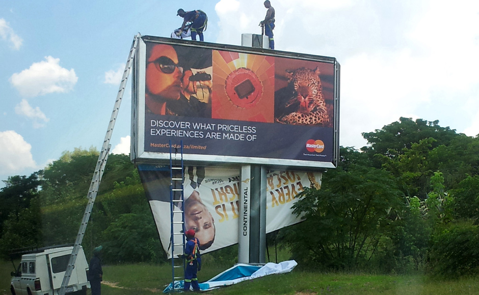 Workers taking down a billboard of Pistorius endorsing a product in Johannesburg. AP