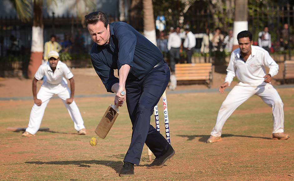 Britain's Prime Minister David Cameron plays cricket with boys at the Oval Maidan, Mumbai. AP