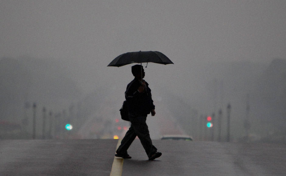 A man crossing the road at Raisina Hill on a gloomy morning. PTI