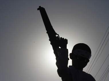 A boy is silhouetted against the sun as he holds a toy gun. Reuters