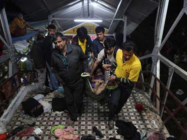 Volunteers carry away an injured person at the Allahabad station: AP