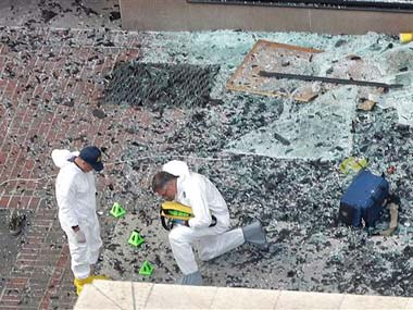 Two men in hazardous materials suits put numbers on the shattered glass and debris as they investigate the scene: AP