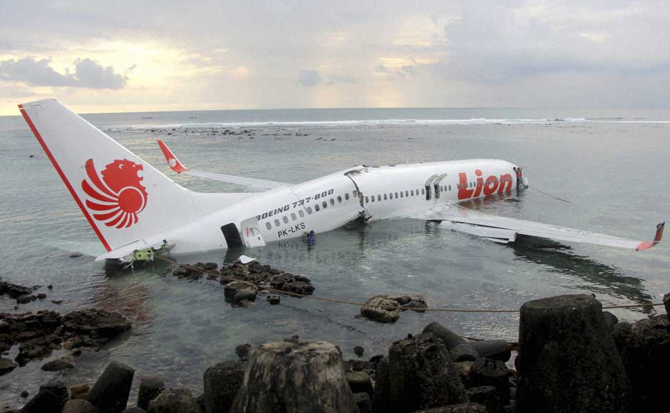 In this photo released by Indonesian Police, a rescue worker stands at the doorway of a crashed Lion Air plane on the water near the airport in Bali, Indonesia on 13 April 2013. AP/PTI