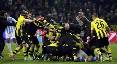 Borussia Dortmund players celebrate after defeating Malaga to win their Champions League quarter-final second leg soccer match. Reuters