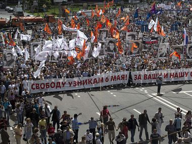 Russian opposition protesters some holding portraits of political prisoners shout anti-Putin slogans as they march through a street next to the Kremlin in Moscow. AP