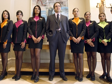 Jeh Wadia, the Managing Director of GoAir, a low fare Indian airlines, stands amidst women, dressed as flight attendants. Reuters