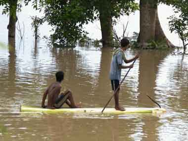 Flood affected people row a banana raft to move to safe place at Bongaon village in Nagaon, Assam on Monday. PTI
