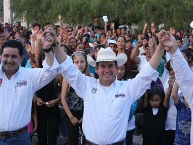 Benjamin Medrano, center, raises his arms with other unidentified people during a campaign event in Chichimequillas, Mexico: AP