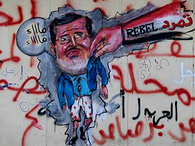 """Graffiti depicting Egypt's Islamist President Mohammed Morsi with an Arabic writing that reads: """"Leave, right"""" covers an outer wall of the presidential palace in Cairo, Egypt. AP"""