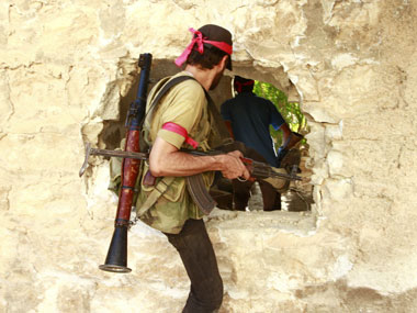 Free Syrian Army fighters move through a hole in a wall in the northern town of Khan al-Assal, after seizing it . Reuters