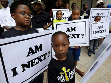 Alvin Duplessis, 10, left, and Thomas McGriff, 5, foreground, hold signs with others from the Watson Memorial Teaching Ministries Church of New Orleans, at a rally held in reaction to the recent George Zimmerman acquittal in New Orleans. AP