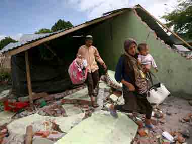 A family carries their belongings after the earthquake in Indonesia. AP