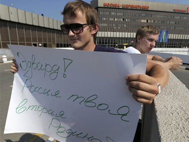 A Russian supporter of  Edward Snowden holds a poster outside Sheremetyevo airport in Moscow. AP