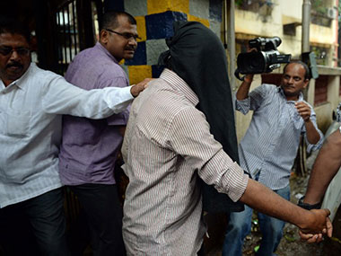 Police officials escort a suspect (C), in the gang-rape of a female photographer, from a crime branch unit station in Mumbai.