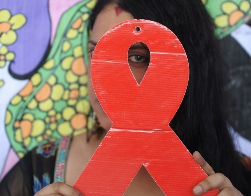 Indian transgender poses with an HIV-AIDS symbol