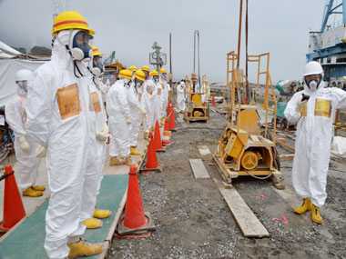 Officials and experts from local towns inspect a coastal embankment where contaminated water leaks occur near Fukushima Dai-ichi nuclear plant. AP