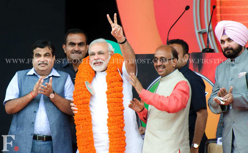 Modi getting garlanded by the Delhi unit of BJP before his speech. Naresh Sharma/Firstpost.