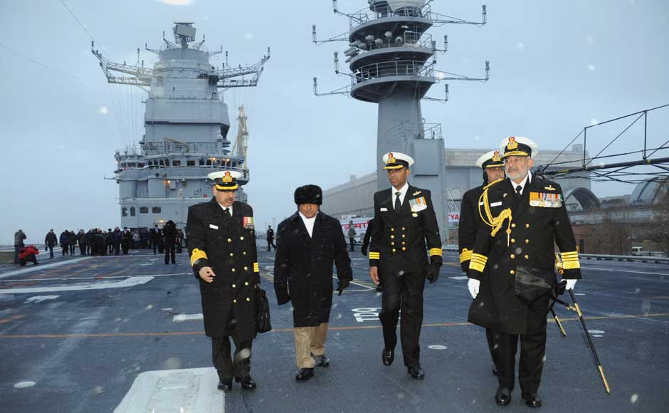 Defence Minister AK Antony walking on the flight deck of INS Vikramaditya, at Sevmash Shipyard in Russia on 16 November 2013. The Chief of Naval Staff, Admiral DK Joshi is also seen. Image courtesy PIB
