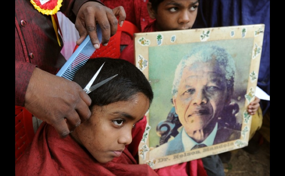 An underprivileged child (L) receives a free haircut from members of the Dr. Nelson Mandela Fans' Forum as another child poses with a portrait of Mandela in Bangalore on July 18, 2011. The charity event was in honour of the 93rd birthday of former South African president and anti-apartheid icon Nelson Mandela. AFP