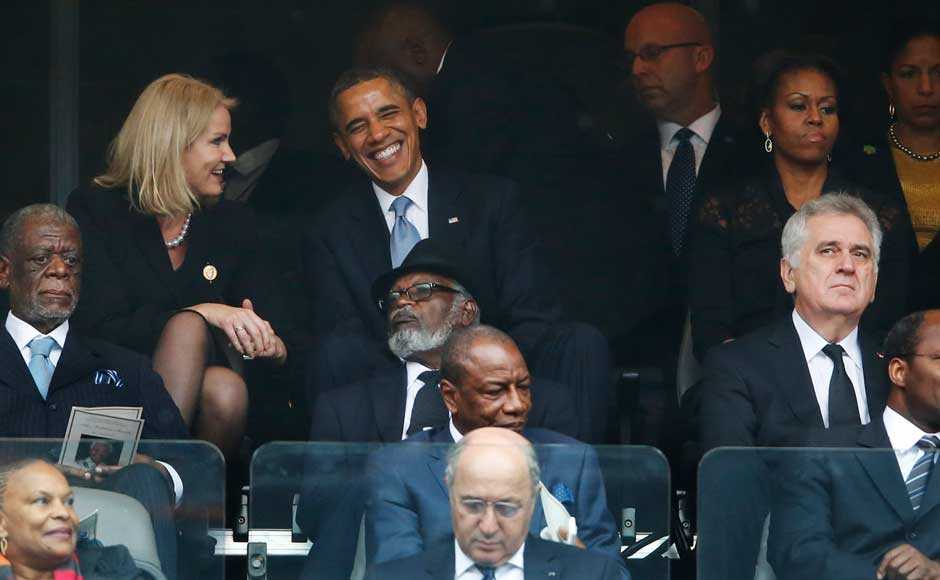 President Barack Obama jokes with Danish prime minister, Helle Thorning-Schmidt, left, as first lady Michelle Obama looks on at right during the memorial service for former South African president Nelson Mandela at the FNB Stadium in Soweto, near Johannesburg, South Africa, Tuesday Dec. 10, 2013. AP