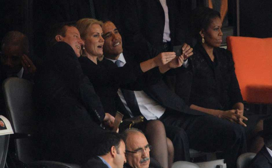 US President  Barack Obama (R) and British Prime Minister David Cameron pose for a selfie with Denmark's Prime Minister Helle Thorning Schmidt (C) next to US First Lady Michelle Obama (R) during the memorial service of South African former president Nelson Mandela at the FNB Stadium (Soccer City) in Johannesburg on December 10, 2013. AFP