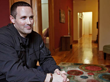 In this Oct. 15, 2013 file photo, Matthew Hurtado talks about The Snuggle House in downtown Madison, Wis.  Customers at Madison's new Snuggle House can snuggle with professional cuddlers for $60 an hour. Supporters say the business helps people relax through non-sexual touch.  But city officials suspect the Snuggle House may be a thinly veiled brothel and cuddling will lead to sexual assault.  Hurtado's past is raising red flags; he has filed for bankruptcy twice, written a book about a sex addict meeting a supernatural being and according to city attorneys has worked as a stripper. AP