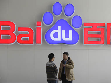 People talk in front of a Baidu's company logo at Baidu's headquarters in Beijing. Reuters