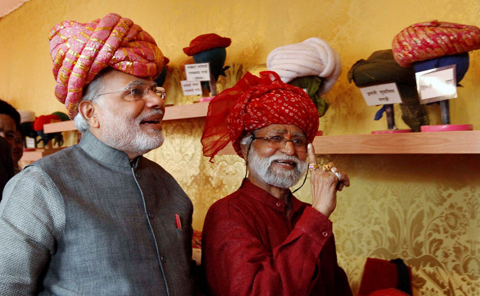 Gujarat Chief Minister and BJP's PM candidate Narendra Modi wears a turban at a stall during inauguration of five-day long handicraft exhibition in Ahmedabad on Friday. PTI