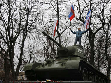A Pro-Russian demonstrator waves Russian and Crimea flags from an old Soviet Army tank during a protest in front of a local government building in Simferopol, Crimea, Ukraine. AP