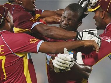 West Indies' players pounce on captain Darren Sammy, second right, to celebrate their win over Australia. AP