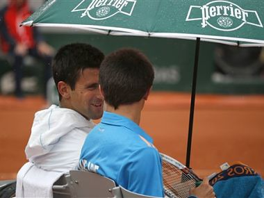 Serbia's Novak Djokovic, left, talks to a ball boy after inviting him to sit on his bench during a break. AP
