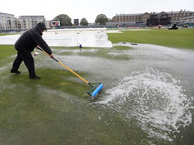 A groundsman tries to sweep water from the field as rain causes the abandonment of play in the 1st England vs India ODI in Bristol. AP