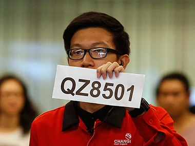 A Changi Airport staff holds up a sign to direct possible next-of-kins of passengers of AirAsia flight QZ 8501 from Indonesian city of Surabaya to Singapore, at Changi Airport in Singapore. Reuters