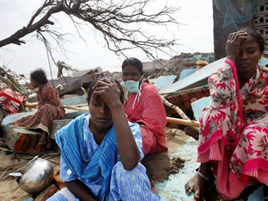 File photo of Lakshmi, center, Selvi, right, and Ariamala, rear with mask, grieve as earthmovers clear debris of their damaged house at a fishermen's colony which was hit by a tsunami, in Nagappattinam. AP