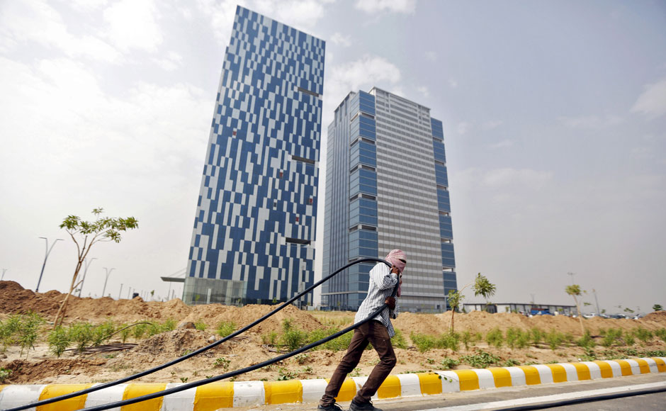 "A labourer pulls a cable in front of two office buildings in Gujarat International Finance Tec-City (GIFT) at Gandhinagar, in the western Indian state of Gujarat, April 10, 2015. India's push to accommodate a booming urban population and attract investment rests in large part with dozens of ""smart"" cities like the one being built on the dusty banks of the Sabarmati river in western India. Picture taken April 10, 2015.  REUTERS"