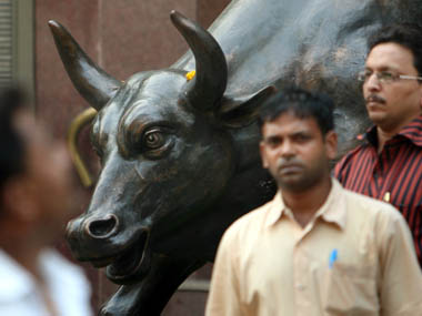 People walk past a bronze replica of a bull at the Bombay Stock Exchange building in Mumbai