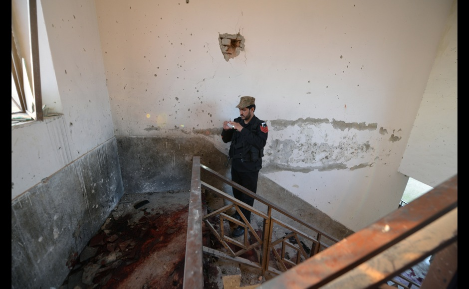 A Pakistani policeman takes photos of stairs splattered with blood, where Taliban militants were killed, at Bacha Khan university following an attack in Charsadda, about 50 kilometres from Peshawar, on January 20, 2016. At least 21 people died in a Taliban assault on a university in Pakistan, where witnesses reported two large explosions as security forces moved in under dense fog to halt the bloodshed. AFP PHOTO / Aamir QURESHI / AFP / AAMIR QURESHI