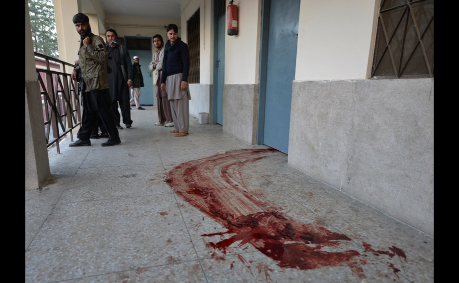 Pakistani policemen stand beside blood on the floor at Bacha Khan university following an attack in Charsadda, about 50 kilometres from Peshawar, on January 20, 2016. At least 21 people died in a Taliban assault on a university in Pakistan, where witnesses reported two large explosions as security forces moved in under dense fog to halt the bloodshed. AFP PHOTO / Aamir QURESHI / AFP / AAMIR QURESHI