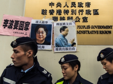 Police walk past missing person notices of Gui Minhai (L), one of five missing booksellers from the Mighty Current publishing house and Yau Wentian (R), a Hong Kong publisher who was last year jailed for 10 years while preparing to release a book critical of Chinese President Xi Jinping, posted on top of the sign of China's Liaison Office in Hong Kong on January 3, 2016. Five missing Hong Kong booksellers were rumoured to have been planning a book about Chinese President Xi Jinping's relationship with a former girlfriend, one of the city's lawmakers said on January 3, as protesters gathered to voice anger over the case. AFP PHOTO / ANTHONY WALLACE / AFP / ANTHONY WALLACE