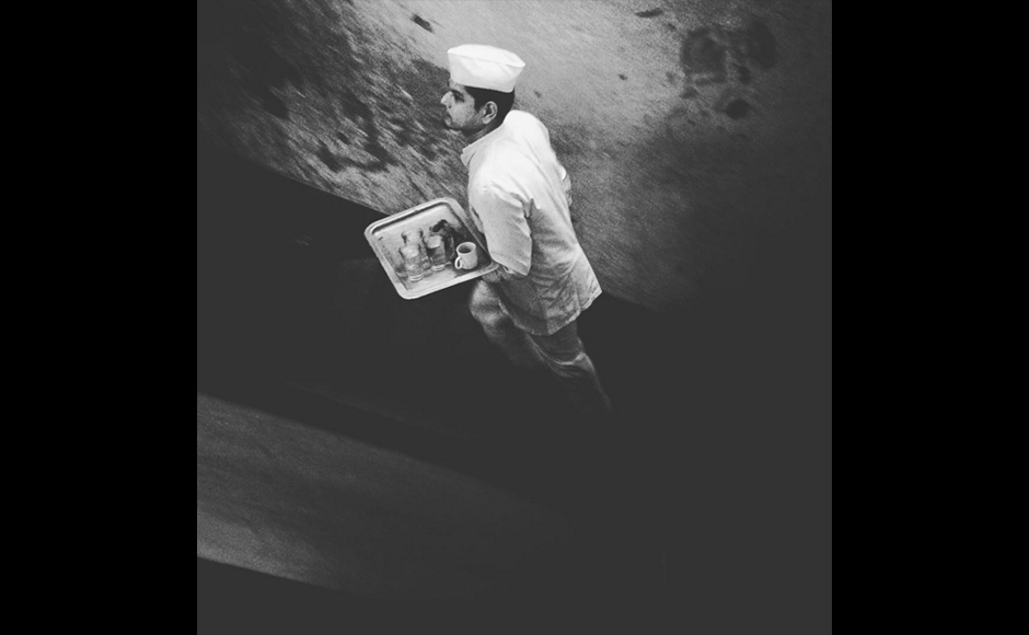 A waiter dressed in a classic white uniform, rushes up the stairs of Kolkata's own Starbucks! The College Street Coffee house with its Victorian charm and classic menu still is a popular hangout, for artists, intellectuals and the young generation of the city. Shot at Indian Coffee House, College Street Kolkata Anindito Mukherjee, 31 years, Photojournalist at Reuters