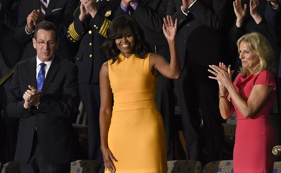 US First Lady Michelle Obama (C) waves, as Jill Biden (R) wife of US Vice President Joe Biden looks on before the arrival of US President Barack Obama before the State of the Union Address during a Joint Session of Congress at the US Capitol in Washington, DC, January 12, 2016. Barack Obama will give his final State of the Union address, perhaps the last big opportunity of his presidency to sway a national audience and frame the 2016 election race. AFP PHOTO / SAUL LOEB / AFP / SAUL LOEB