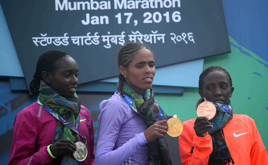Second-placed runner Bornes Kitur, (L), winner Shuko Genemo (C) and third-placed Valentine Kipketer hold their medals after the Standard Chartered Mumbai Marathon 2016 in Mumbai, India on January 17, 2016. (Pravin Utturkar/SOLARIS IMAGES)