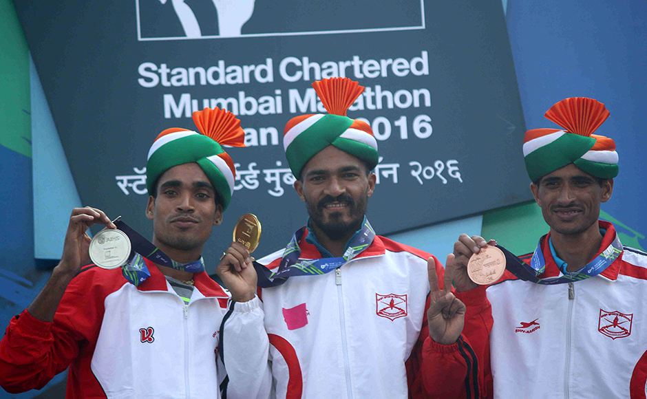 (L to R) Indian athletes Gopi T, Nitenrra Singh Rawat and Kheta Ram hold their medals after the Standard Chartered Mumbai Marathon 2016 in Mumbai, India on January 17, 2016. (Pravin Utturkar/SOLARIS IMAGES)