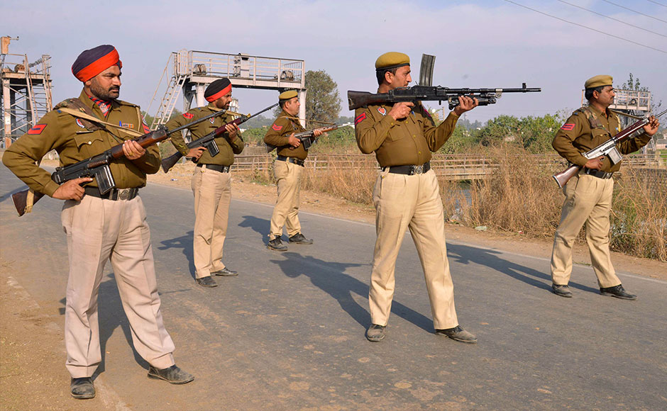 Indian police personnel stand alert outside an airforce base in Pathankot on January 2, 2016, during an ongoing attack on the base in the northern Indian state of Punjab by suspected militants. Suspected Islamist gunmen have staged a pre-dawn attack on a key Indian air base near the Pakistan border with two militants killed in a shootout, officials said, striking a blow to the neighbours' fragile peace process. AFP PHOTO/NARINDER NANU