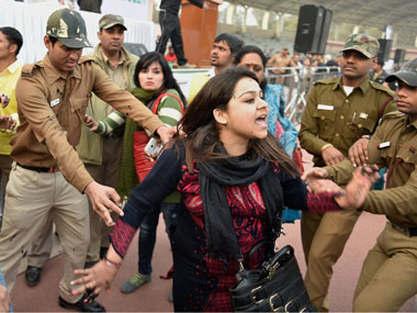 "Policemen try to control a member of Aam Aadmi Sena after she splattered Delhi CM Arvind Kejriwal with ink while protesting against the CNG scam, at a ""thanksgiving rally following the ""success"" of his government's odd-even scheme at Chhatrasal Stadium, in New Delhi on Sunday. PTI"